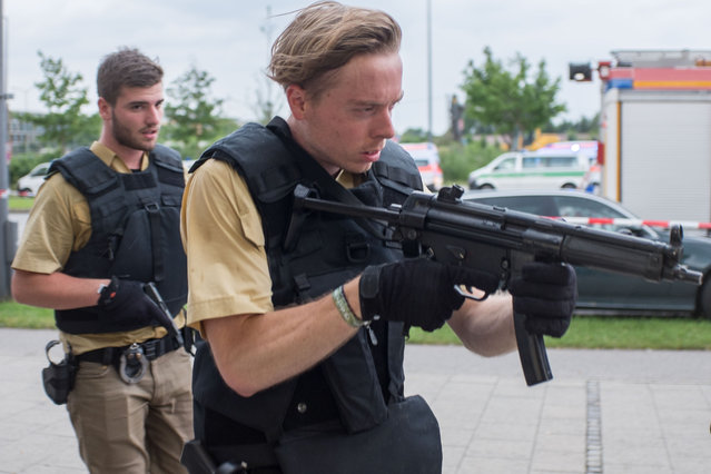 Armed policemen arrive at a shopping centre in which a shooting was reported in Munich, southern Germany, Friday, July 22, 2016. Situation after a shooting in the Olympia shopping centre in Munich is unclear. (Photo by Matthias Balk/DPA via AP Photo)
