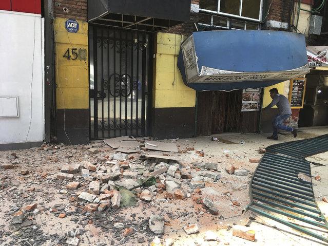 A man enters a damaged building after an earthquake in Mexico City, Tuesday, September 19, 2017. (Photo by Eduardo Verdugo/AP Photo)