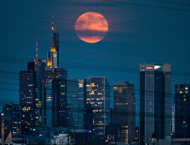 The full moon rises over the bank buildings in Frankfurt, Germany, late Monday, June 17, 2019. (Photo by Michael Probst/AP Photo)