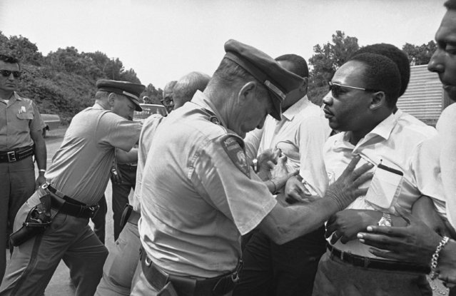 In this June 7, 1966 file photo, Mississippi Highway Patrolmen shove the Rev. Martin Luther King and members of his marching group off the traffic lane of Highway 51 south of Hernando, Miss. King, Student Non-Violent Coordinating Committee leader Stokely Carmichael (head visible at upper right) and other civil rights leaders had taken up the march begun by James Meredith. (Photo by AP Photo)