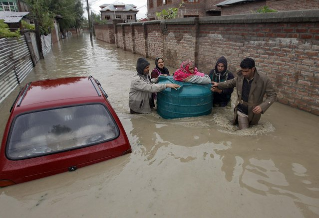 People transport a sick woman in an empty water tank on a flooded street during rain in Srinagar September 5, 2014. Sixty-five people were killed after heavy rains caused flash floods in Indian-administered Kashmir, including a wedding party on a bus that was swept away, officials said on Thursday. Authorities declared a disaster alert in the northern region after two days of heavy rain hit villages across the Kashmir valley, causing the worst flooding in two decades. (Photo by Danish Ismail/Reuters)