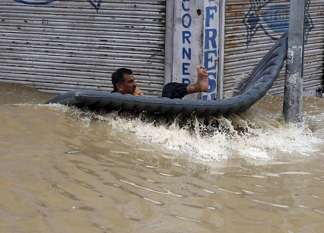 A Kashmiri man looses his balance on his makeshift boat after he was hit by a wave as he tries to travel to safer place in Srinagar September 7, 2014. Authorities declared a disaster alert in the northern region after heavy rain hit villages across the Kashmir valley, causing the worst flooding in two decades. (Photo by Danish Ismail/Reuters)