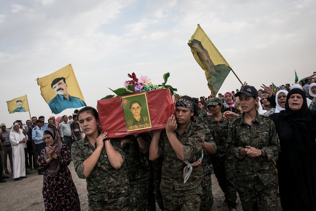 At a funeral procession YPJ soldiers carry the casket of fellow female soldier, Evrim, who died in combat while fighting IS; in Derek City, Roshava, Syria on August 18, 2014. Rojava experiences several funerals a month due to the recent intense fighting conditions with IS in the region – about 24 YPG / YPJ soldiers were buried during the month of August in the cememtery pictured here.  (Photo by Erin Trieb/NBC News)