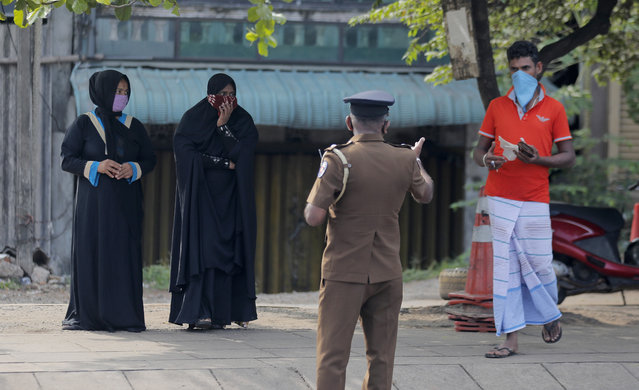 A Sri Lankan police officer detains curfew violators during a curfew imposed to curb the spreading of new coronavirus in Colombo, Sri Lanka, Wednesday, April 1, 2020. (Photo by Eranga Jayawardena/AP Photo)