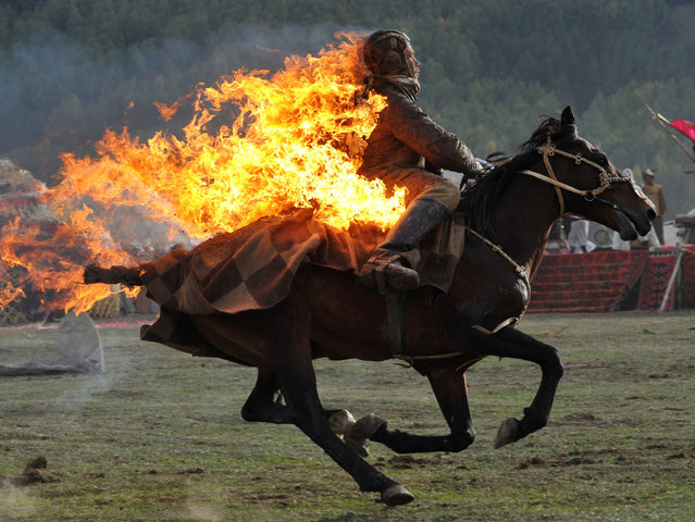 Photo taken on September 10, 2014 shows a Kyrgyz stuntman performing during the first World Nomad Games in the Kyrchin (Semenovskoe) gorge, some 300 km from Bishkek. Teams of Azerbaijan, Kazakhstan, Belarus, Mongolia and Tajikistan take part in the games. (Photo by Vyacheslav Oseledko/AFP Photo)