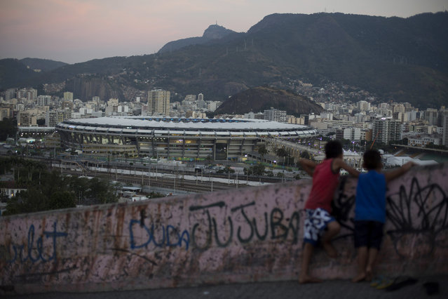 Two boys look out from the Mangueira slum towards the Maracana Stadium that is hosting the Rio's 2016 Summer Olympics opening ceremonies, in Rio de Janeiro, Brazil, Friday, August 5, 2016. (Photo by Leo Correa/AP Photo)