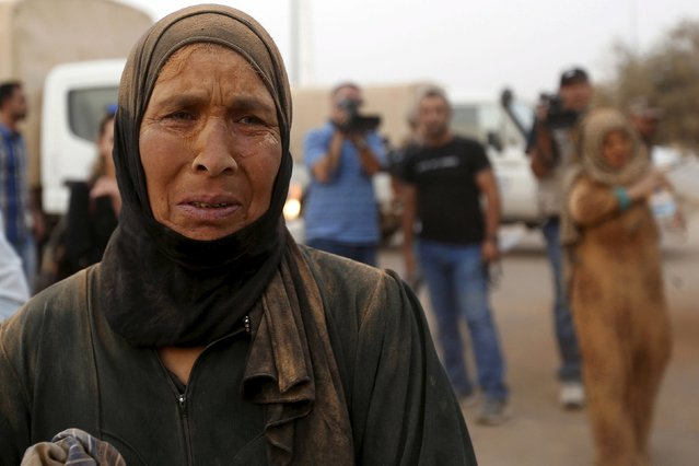 A Syrian refugee woman covered with dust cries after arriving at the Trabeel border, after she crossed into Jordanian territory with her family, near the northeastern Jordanian border with Syria, and Iraq, near the town of Ruwaished, east of Amman September 10, 2015. (Photo by Muhammad Hamed/Reuters)
