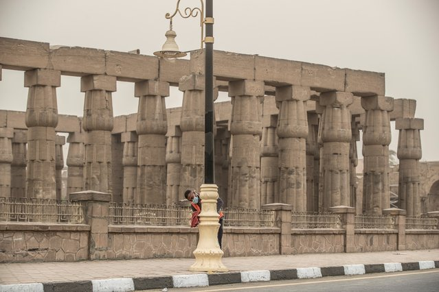 A municipality worker cleans lamp posts amid a sandstorm and coronavirus fears outside the Luxor Temple in Egypt's southern city of Luxor on March 12, 2020. (Photo by Khaled Desouki/AFP Photo)