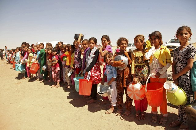 Displaced people from the minority Yazidi sect, fleeing violence in the Iraqi town of Sinjar west of Mosul, line up to receive food at the khanki camp on the outskirts of Dohuk province, September 13, 2014. (Photo by Ari Jalal/Reuters)