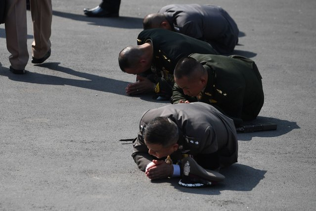 Members of the military prostrate as the Royal Urn passes during the funeral procession for the late Thai king Bhumibol Adulyadej in Bangkok on October 26, 2017. A sea of black- clad mourners massed across Bangkok' s historic heart early on October 26 as funeral rituals began for King Bhumibol Adulyadej, a revered monarch whose passing after a seven- decade reign has left Thailand bereft of its only unifying figure. (Photo by Roberto Schmidt/AFP Photo)