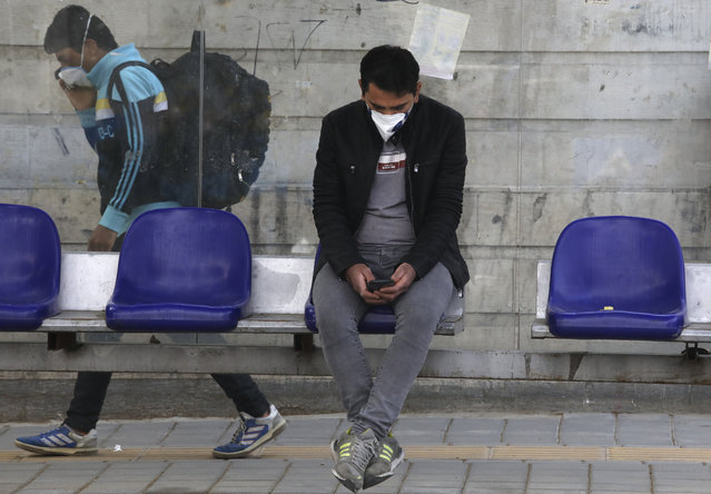 A man wearing a face mask to curb the spread of the new coronavirus sits at a bus stop, as another man walks past, in Niavaran in northern Tehran, Iran, Thursday, April 16, 2020. Authorities have canceled ceremonies marking the anniversary of the death of Ayatollah Khomeini, the founder of the Islamic Republic over COVID-19 disease concerns, which underscored Iranian officials' expectation that the virus crisis will continue for several more weeks. (Photo by Vahid Salemi/AP Photo)