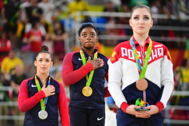 From right to left, Russia's Aliya Mustafina, USA's Simone Biles and USA's Alexandra Raisman on the podium of the women's individual all-around gymnastics final, August 11, 2016. Biles won the gold medal, and Rasiman took home the silver. (Photo by Emmanuel Dunand/AFP Photo)