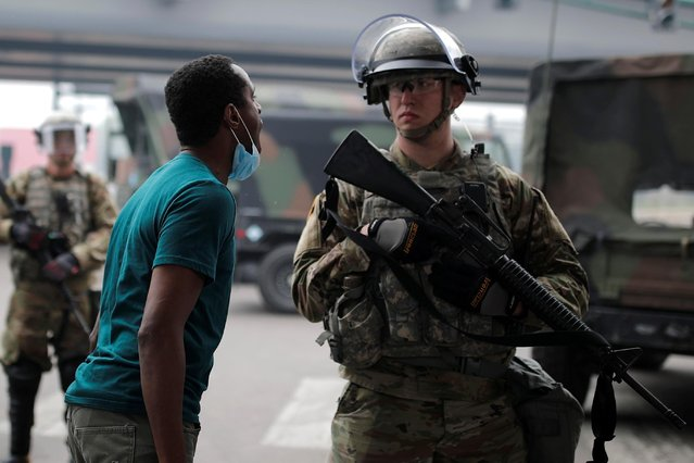 A man confronts a National Guard member as they guard the area in the aftermath of a protest against the death in Minneapolis police custody of African-American man George Floyd, in Minneapolis, Minnesota, U.S., May 29, 2020. (Photo by Carlos Barria/Reuters)
