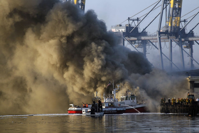 Los Angeles Firefighters watch as smoke from a dock fire rises at the Port of Los Angeles in the Wilmington section of Los Angeles on Tuesday, September 23, 2014. The fire that forced evacuations from the wharf continues to smolder but officials say it's under control. Nearly 12 hours after starting, the blaze is sending up huge plumes of smoke that is drifting over Los Angeles Harbor early Tuesday. (Photo by Nick Ut/AP Photo)