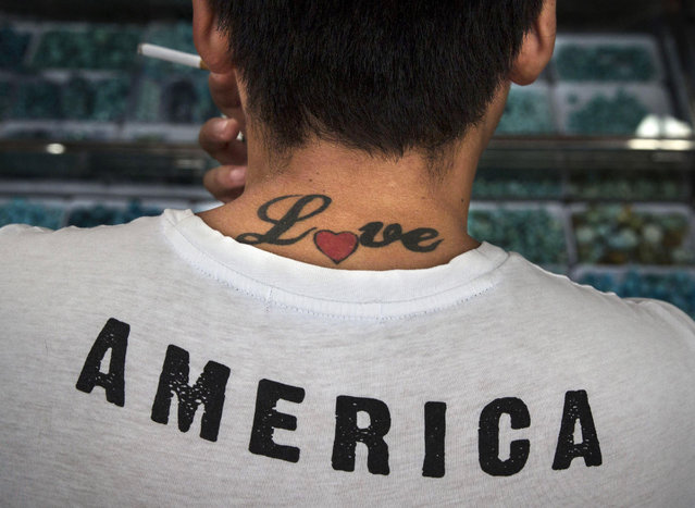 A Chinese man sports a tattoo as he shops at a local antique market on September 19, 2014 in central Beijing, China. (Photo by Kevin Frayer/Getty Images)