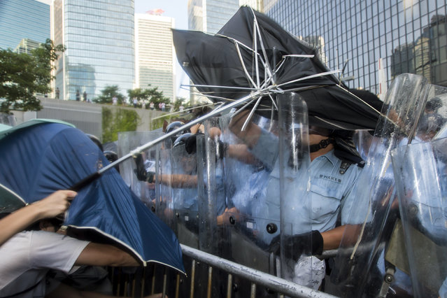 Pro-democracy students scuffle with riot police after hundreds of protesters stormed into a restricted area at the government headquarters in Hong Kong September 27, 2014. (Photo by Tyrone Siu/Reuters)
