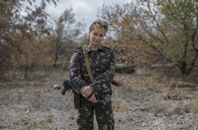 A woman fighting on the side of pro-Russian rebels poses with her rifle in the town of Nizhnaya Krinka, eastern Ukraine, September 23, 2014. (Photo by Marko Djurica/Reuters)
