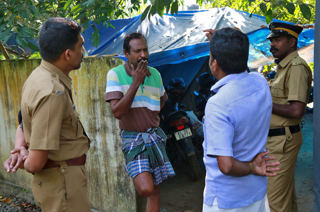 K M Ashokan (2-L), father of 24-year-old Akhila, who converted to Islam in 2016 and took a new name, Hadiya, smokes while speaking with a friend, as police officers stand guard outside his house at Vaikom in the Kottayam district of the southern state of Kerala, India November 23, 2017. (Photo by Sivaram V/Reuters)