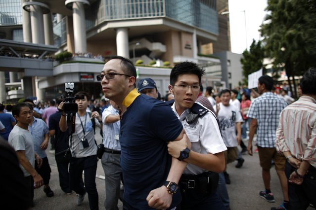 A policeman (front R) removes an anti-Occupy Central protester from the main protest site in Admiralty in Hong Kong, October 13, 2014. (Photo by Carlos Barria/Reuters)