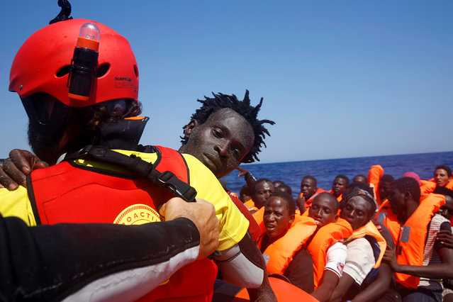 A migrant is carried from an overcrowded dinghy by a member of the Spanish NGO Proactiva during a rescue operation by the Spanish NGO Proactiva, off the Libyan coast in Mediterranean Sea August 28, 2016. (Photo by Giorgos Moutafis/Reuters)