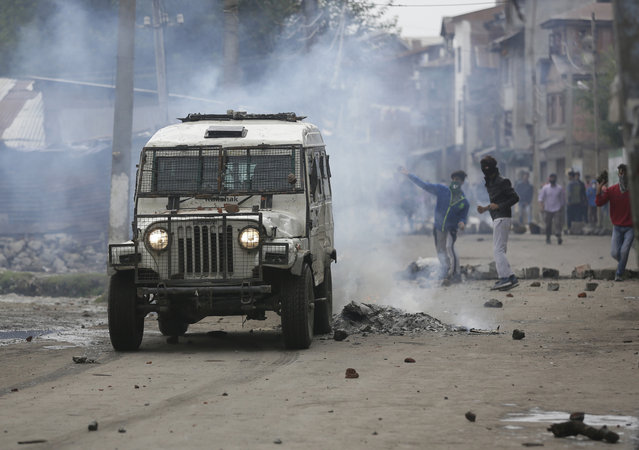 Kashmiri protesters throw stones at a police vehicle during a protest after curfew was lifted in some parts of Srinagar, Indian-controlled Kashmir, Monday, August 29, 2016. Authorities on Monday lifted a curfew imposed in most parts of Indian-controlled Kashmir as part of a 52-day security lockdown, although most shops and businesses remained closed due to an ongoing strike called to protest Indian rule in the disputed Himalayan region. (Photo by Mukhtar Khan/AP Photo)