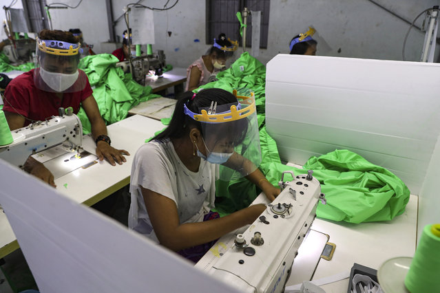 Workers wearing face mask and face shield to help curb the spread of the new coronavirus, sew behind white partition surrounding their sewing tables as they work at a garment factory Thursday, May 28, 2020, at Industrial Zone in Yangon, Myanmar. Despite a poor public health infrastructure and crowded urban areas, Myanmar has reported a surprising low number of COVID-19 cases, with just a little over 200 confirmed and a few deaths. (Photo by Thein Zaw/AP Photo)