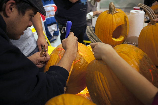 Chris Soria of the Maniac Pumpkin Carvers helps a workshop attendee cut open a pumpkin to empty it's innards at Cotton Candy Machine in Brooklyn, N.Y. on October 18, 2014. (Photo by Siemond Chan/Yahoo Finance)