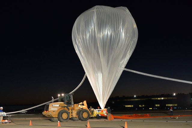 In this photo provided by Paragon Space Development Corporation, a balloon is prepared that will carry Google executive Alan Eustace into the stratosphere in his leap from the edge of space that broke the sound barrier and set several skydiving records over the southern New Mexico desert outside Roswell Friday, October 24, 2014. (Photo by AP Photo/Paragon Space Development Corporation)