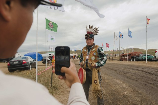 Aaron Makwa Chivis takes a photo of his friend Joe Syette after they travelled from the Saginaw Chippewa Reservation in Mount Pleasant, Michigan to join an encampment where hundreds of protestors have gathered on the banks of the Cannon Ball River to stop construction of the Energy Transfer Partners' Dakota Access oil pipeline near the Standing Rock Sioux reservation in Cannon Ball, North Dakota, U.S.. September 7, 2016. (Photo by Andrew Cullen/Reuters)