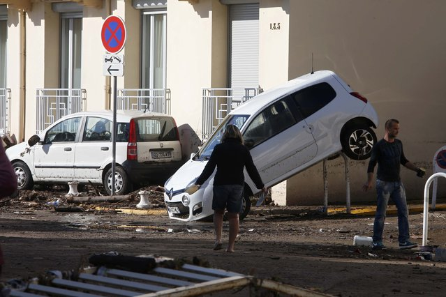 People look at damaged cars after flooding caused by torrential rain in Cannes, France, October 4, 2015. Flooding along part of the French Riviera has killed least 13 people, officials said Sunday. The downpour hit the Alpes-Maritimes region, which lies at the eastern end of France's Mediterranean coast and borders Italy, on Saturday evening. (Photo by Eric Gaillard/Reuters)
