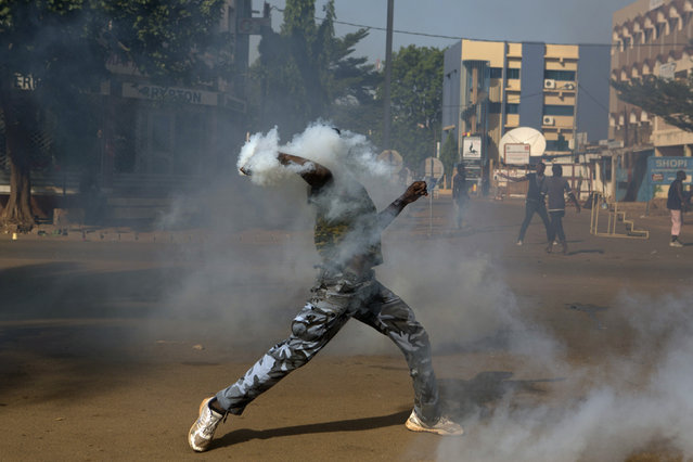 An anti-government protester throws a tear gas canister at riot police in Ouagadougou, capital of Burkina Faso, October 30, 2014. (Photo by Joe Penney/Reuters)
