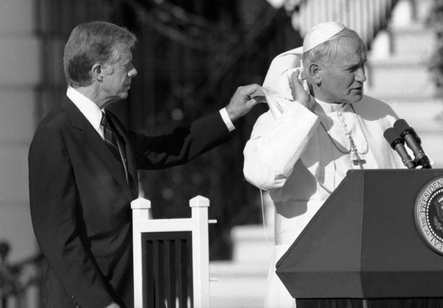 U.S. President Jimmy Carter gives Pope John Paul II a hand with his cape, blown up by a breeze during ceremonies on the South Lawn of the White House in Washington, Saturday, October 6, 1979. (Photo by AP Photo)