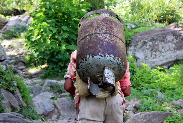 A boy carries a gas canister on a road to Dhalamlam Mountain in the Jafariya district of the western province of Raymah, Yemen May 20, 2016. (Photo by Abduljabbar Zeyad/Reuters)