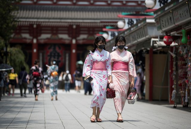 Two women in traditional kimonos wear face masks to help curb the spread of the coronavirus as they visit the Sensoji temple in Tokyo on Friday, August 7, 2020. (Photo by Hiro Komae/AP Photo)