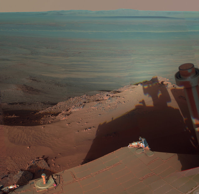 Opportunity catches its own late-afternoon shadow in a view eastward across Endeavour Crater on Mars. The rover used a panoramic camera between about 4:30 and 5:00 p.m. local Mars time to record images taken through different filters and combined into this mosaic view. The view is presented in false color to make some differences between materials easier to see, such as the dark sandy ripples and dunes on the crater's distant floor. (Photo by AP Photo/NASA/JPL-Caltech/Cornell/ASU/The Atlantic)