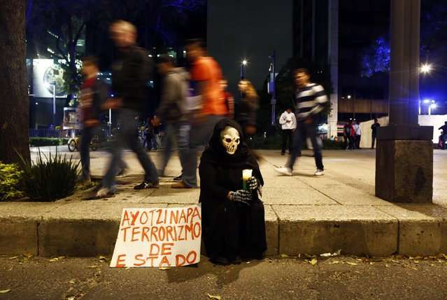 A person in a disguise sits on a sidewalk holding a candle during a protest denouncing the apparent massacre of 43 trainee teachers in Mexico City late November 8, 2014. Protesters tried to set the wooden door of Mexican President Enrique Pena Nieto's ceremonial palace on fire in the historic center. (Photo by Edgard Garrido/Reuters)