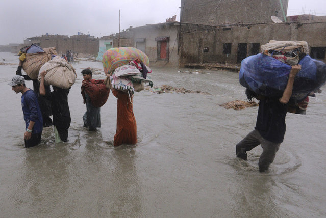 Local residents carry salvaged belongings as they wade through a flooded area during a heavy monsoon rain in Yar Mohammad village near Karachi, Pakistan, Thursday, August 27, 2020. Pakistan's military said it will deploy rescue helicopters to Karachi to transport some 200 families to safety after canal waters flooded the city amid monsoon rains. (Photo by Fareed Khan/AP Photo)