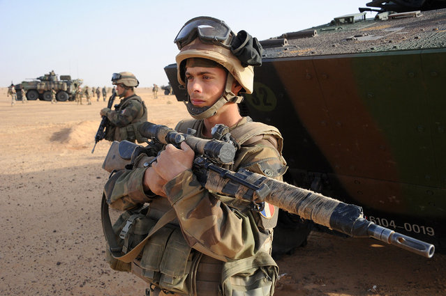 A French army sniper stands next to an armored vehicle outside Bourem, Mali, on February 17, 2013. (Photo by Pascal Guyot/AP Photo/The Atlantic)