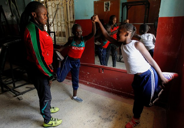 Kenyan weightlifter Mercy Obiero watches as her daughter Chanel Okoth and granddaughter Keysha Atiky stretch after a training session at a gym within Umoja estate in Nairobi, Kenya on September 18, 2020. (Photo by Monicah Mwangi/Reuters)