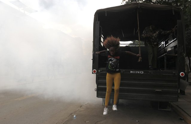 A detained protester jumps from a police truck as she escapes after riot police released teargas to disperse the #OccupyHarambeeAve demonstration in Kenya's capital Nairobi November 25, 2014. (Photo by Thomas Mukoya/Reuters)