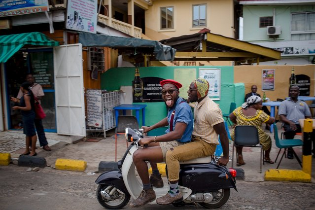 DJ Evans Mireku Kissi (R) and fashion stylist Daniel Quist ride a motorcycle in front of a street side bar in Accra, Ghana. June 10, 2015. (Photo by Francis Kokoroko/Reuters)