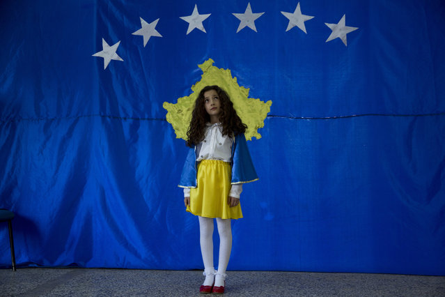 "A student named Pavarsia Sopi, 10 poses for a photo in front of flag of Kosovo during an independence celebration ceremony at a school in the village of Sllovi near the town of Lipjan, Kosovo on Friday February 16, 2018, ahead of the upcoming 10th independence anniversary. A student of the school, Pavaresia Sopi, 10, was the first child born after Kosovo declared independence from Serbia in 2008. Pavaresia translates in English as ""Independence"". (Photo by Visar Kryeziu/AP Photo)"
