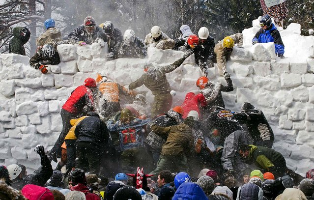 People storm a snow castle during celebrations of Maslenitsa, or Shrovetide, outside Marfino village, 32 miles north of Moscow, on March 17, 2013. Maslenitsa is a traditional Russian holiday marking the end of winter that dates back to pagan times. (Photo by Yevgeny Feldman/Associated Press)