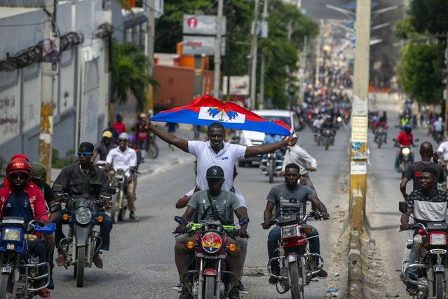 A protester holds up a Haitian national while riding on a motorcycle during a protest to demand the resignation of President Jovenel Moise in Port-au-Prince, Haiti, Saturday, October 17, 2020. (Photo by Dieu Nalio Chery/AP Photo)