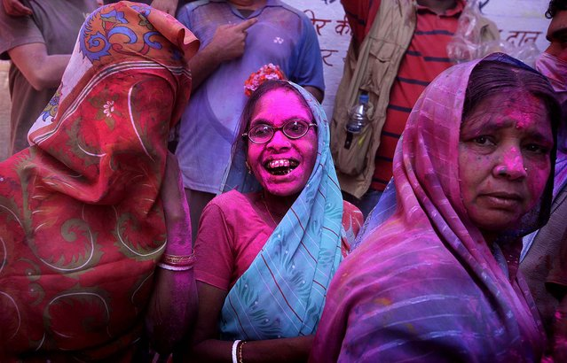 An elderly Indian Hindu woman and other devotees react as they are covered with colored powder. (Photo by Manish Swarup/Associated Press)
