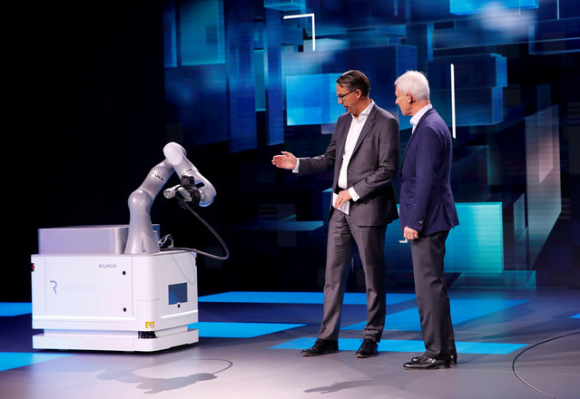 Dr. Till Reuter CEO of Kuka and Volkswagen CEO Matthias Mueller present a robot for the charging of electric cars during the press day at the 88th Geneva International Motor Show in Geneva, Switzerland on Tuesday, March 6, 2018. (Photo by Denis Balibouse/Reuters)