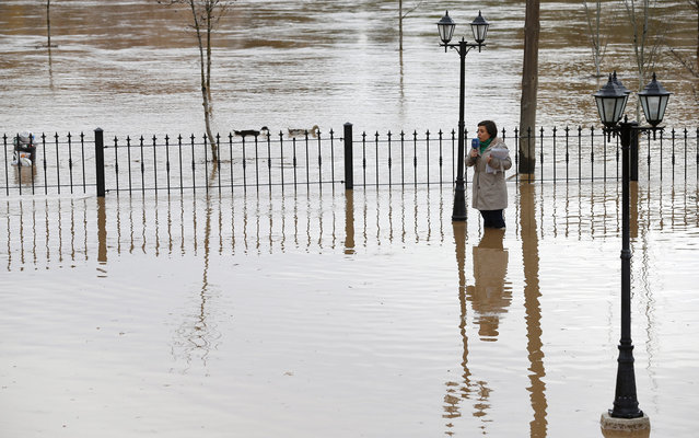 A television journalist standing in floodwaters reports the situation in Tordesillas after the Duero river overflowed its banks on April 1, 2013. Spain suffered its wettest March since 1947, according to information released by the Spanish meteorological agency AEMET. (Photo by Cesar Manso/AFP Photo)