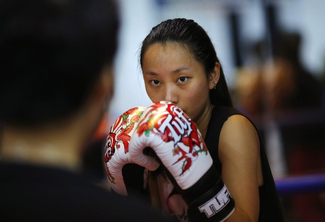 A woman attends a boxing class at Princess Women's Boxing Club in Shanghai December 3, 2014. Women have boxed as long as the sport has existed but for years they were relegated out of national and international competitions in many countries around the world. Female boxers entered the ring in an exhibition match at the 1904 Olympic Games, but it was more than a century later when they were given the green light to make their Olympic debut in London in 2012. (Photo by Carlos Barria/Reuters)