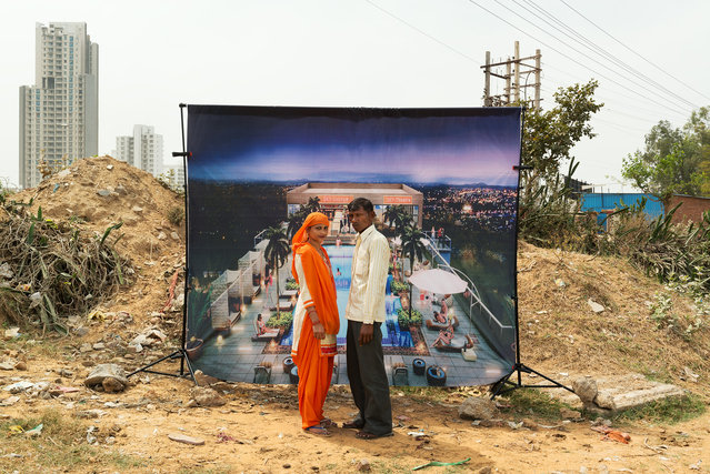 "Luxury Living Bhiwadi: ""Sky Club on 18th Floor"". Passersby, workers and villagers pose in front of the idealised representations of modern homes. (Photo by Arthur Crestani/The Guardian)"