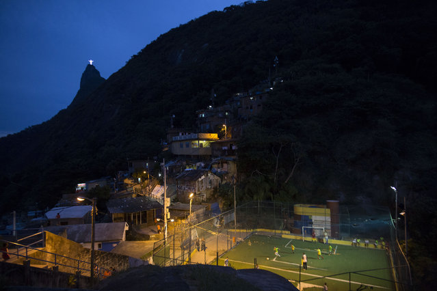 In this June 6, 2014 file photo, people play soccer in the Dona Marta slum, backdropped by the Christ the Redeemer statue and Corcovado Mountain in Rio de Janeiro, Brazil. Soccer schools operate in nearly all of the slums, from the Dona Marta shantytown, which is ensconced in the middle-class Botafogo neighborhood, to Mangueira, a historic slum overlooking the mythical Maracana Stadium. (Photo by Felipe Dana/AP Photo)